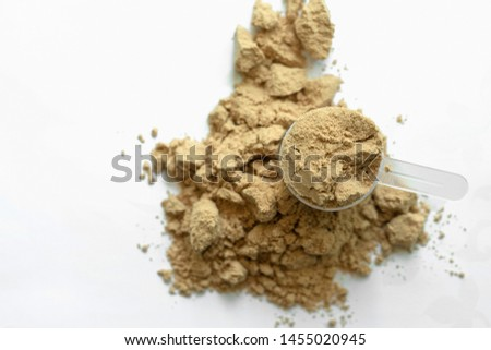 Scoop of whey protein with isolated white background. top view