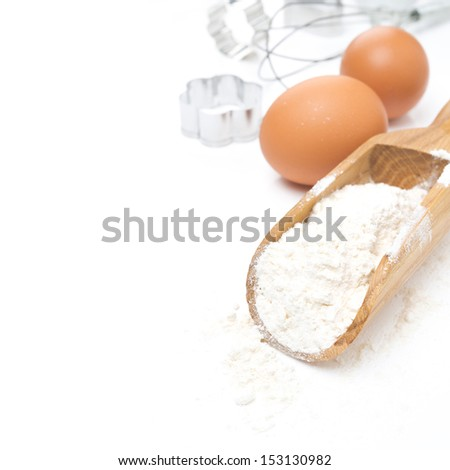 scoop with flour, eggs and cookie cutters isolated on white