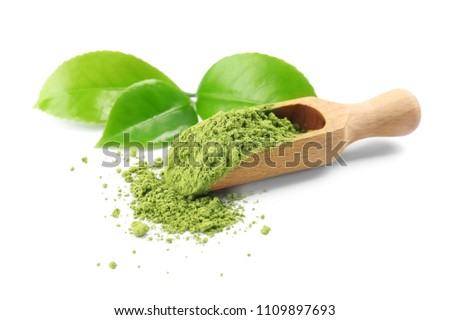 Scoop with powdered matcha tea and green leaves on white background