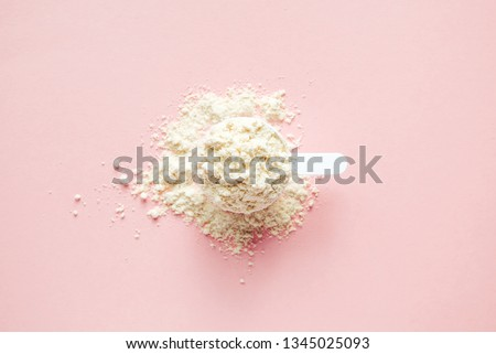 Scoop with protein powder on pink background. Top view sports nutrition minimal concept. #1345025093