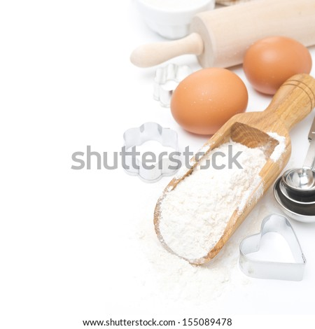 scoop with wheat flour, rolling pin, eggs and cookie cutters isolated on white