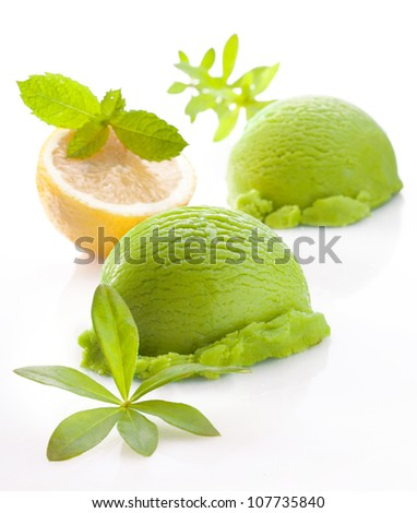 Scoops of fresh green lemon or lime icecream on a white studio background with faint reflection