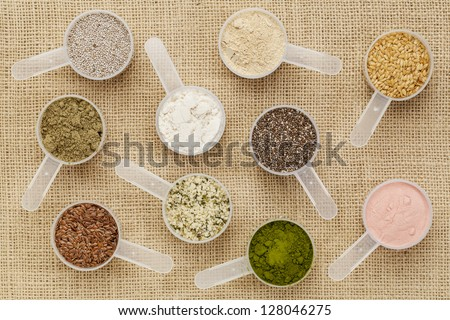 scoops of superfood - healthy seeds and powders (white and black chia, flax, hemp, pomegranate fruit powder, wheatgrass, hemp and whey protein, maca root) on canvas #128046275