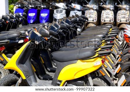 scooter bikes in rental shop in a row arrangement