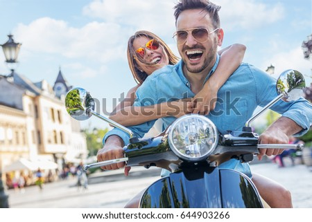 Scooter ride. Beautiful young couple riding scooter together. Focus on girl.