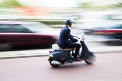 scooter rider on a bike lane in the busy city traffic in motion blur