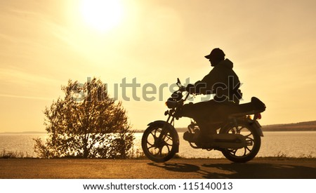 Scooter standing on a hill in the sunset
