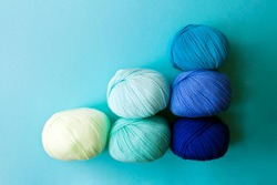 Scoring system in the form of skeins of yarn on a blue background. A graph in the form of a nuanced gradient. Arranged balls  of yarn.