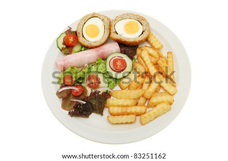 Scotch egg and ham salad with chips on a plate isolated against white