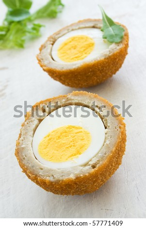 Scotch egg on a white board with green salad