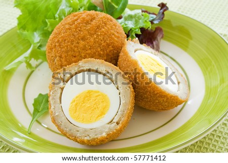 Scotch eggs on a plate with a green salad