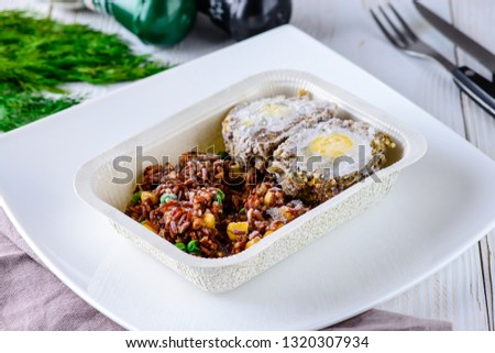 Scotch eggs with beef and brown rice, prepared frozen meal, container tv dinner. Microwave meals ready to heat up