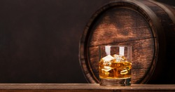 Scotch whiskey glass and old wooden barrel. With copy space