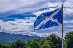 Scotland flag waving wind cloudy day at Loch Ness Highlands