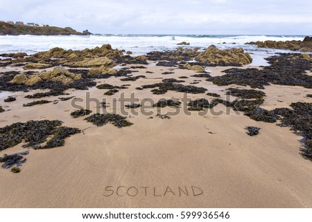 Scotland inscribed on wet yellow rocky beach sand. #599936546