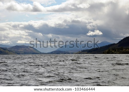Scotland Loch Ness view. Water, mountains, black clouds and one little white cloud.