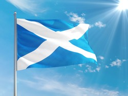 Scotland national flag waving in the wind against deep blue sky. High quality fabric. International relations concept.
