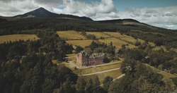 Scotland ocean coast landscape aerial view: forests, valleys, hills. Brodick castle - historical ancient building in Arran Island. Road with riding cars.