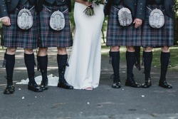 Scotsmen dressing in kilt on wedding day with bride in the middle