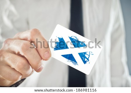 Scottish Businessman holding business card with Scotland Flag. International cooperation, investments, business opportunities concept.