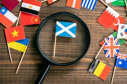 Scottish flag. Flags of many countries, magnifying glass on wooden table