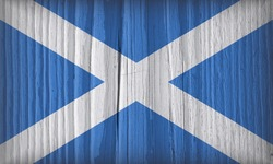 Scottish flag on a dry wooden surface. Wallpaper or backdrop made of old wood. Natural background with vignetting. Rough board with cracks. The official symbol of Scotland. Hard shadows
