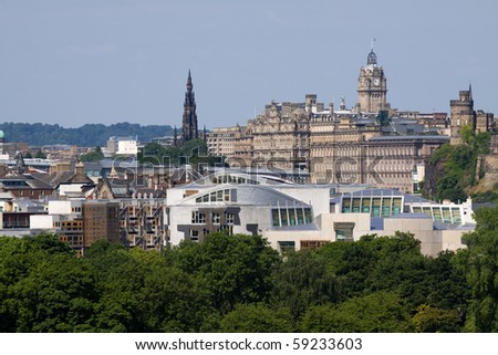 Scottish Parliament and Princes St with the Balmoral clock tower and Scott Monument visible in the background.