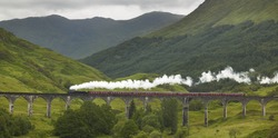 Scottish steam train passing a classic bridge. Horizontal