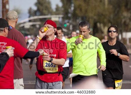SCOTTSDALE, AZ - JANUARY 17:    Unidentified runners hydrate at a  hydration station at the P.F. Chang's  Phoenix Arizona Marathon on January 17, 2010 in Scottsdale, AZ. - stock photo
