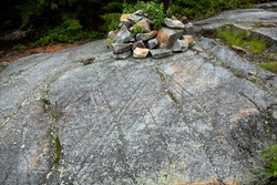 Scoured granite bedrock, with glacial striations and grooves, and a rock cairn at the bald summit of Mt. Kearsarge in Wilmot, New Hampshire.
