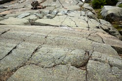 Scoured granite bedrock, with glacial striations and grooves, and a rock cairn in a hiking trail at the summit of Mt. Kearsarge in Wilmot, New Hampshire.