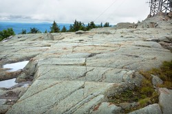 Scoured granite bedrock, with glacial striations and grooves, in a hiking trail at the summit of Mt. Kearsarge in Wilmot, New Hampshire.