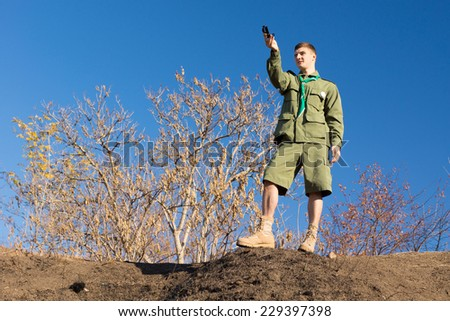 Scout standing on a rock taking a compass reading to get his bearing and location, low angle skyline view