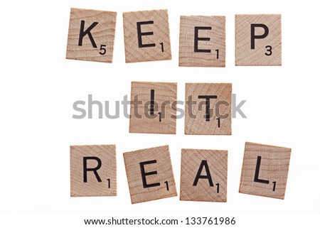 scrabble letters spelling keep it real on white background