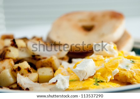 scrambled egg and melted goat cheese with a toasted bagel and home made hash browns