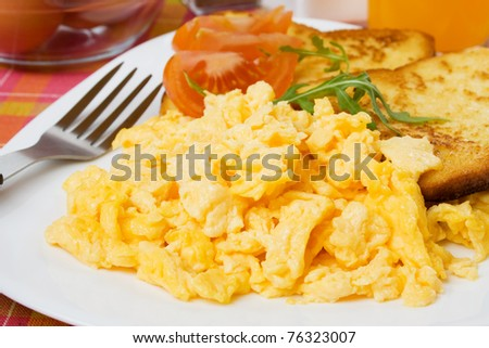 Scrambled egg served with french toast and tomato