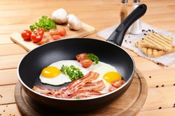 Scrambled eggs and bacon on frying pan on table close-up