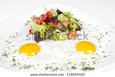 Scrambled eggs - fried eggs with vegetables and greens with fresh salad is on a white plate - stock photo