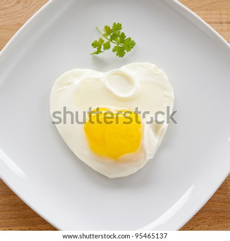Scrambled eggs in a heart on a white plate, standing on a wooden table, a square crop