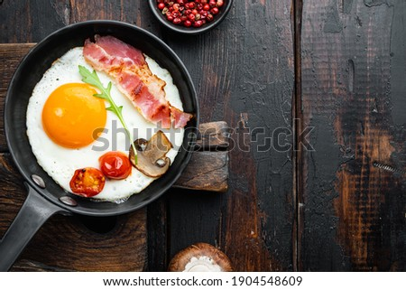 Scrambled eggs in frying pan with pork lard, bread and green feather in cast iron frying pan, on old dark wooden table background, top view flat lay , with space for text copyspace