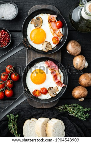 Scrambled eggs in frying pan with pork lard, bread and green feather in cast iron frying pan, on black wooden table background, top view flat lay