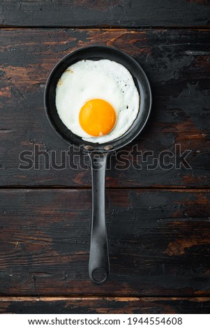 Scrambled eggs in frying pan with pork lard, bread and green feather in cast iron frying pan, on old dark wooden table background, top view flat lay