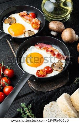 Scrambled eggs in frying pan with pork lard, bread and green feather in cast iron frying pan, on black wooden table background