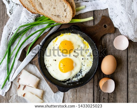 Scrambled eggs in frying pan with pork lard, bread and green feathers onions on old wooden table. National Ukrainian or belorussian food. Breakfast, lunch. Top view, selective focus, rustic style Stock foto ©