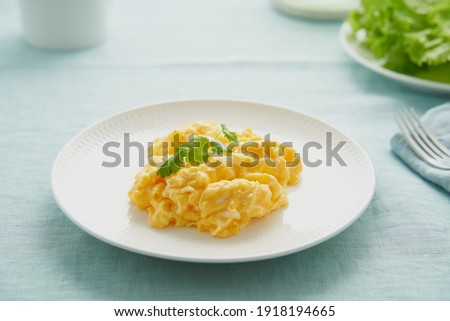 Scrambled eggs, omelette. Breakfast with pan-fried eggs. Texture of omelet on white plate on green mint linen textile tablecloth. Keto ketogenic diet. Soft light