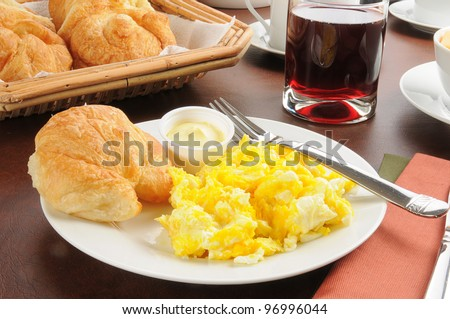 Scrambled eggs on a plate with a croissant