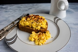 Scrambled eggs on wholegrain bread wit spices, foodphotography concept