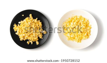 Scrambled eggs or omelet on black and white plates isolated. Breakfast fried eggs stirred or beaten together, morning hot omelette, fresh omlet top view Stok fotoğraf ©