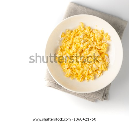 Scrambled eggs or omelet on white plate isolated. Breakfast fried eggs stirred or beaten together with salt and butter. Morning hot omelette, fresh omlet top view Stok fotoğraf ©