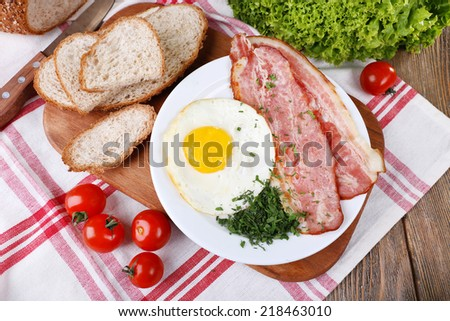 Scrambled eggs with bacon and vegetables served on plate on napkin